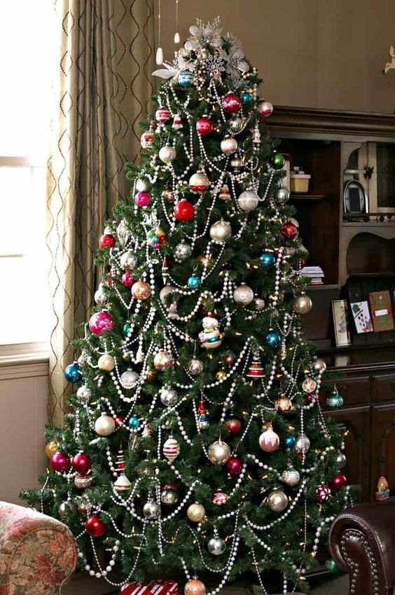 a Christmas tree with colorful vintage ornaments and beaded garlands plus lights for a chic and bold look