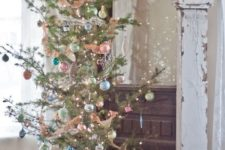a Christmas tree with lights and pastel ornaments of various colors for a chic vintage feel