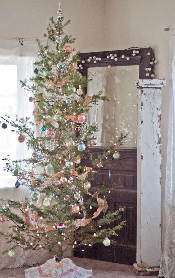 un sapin de Noël avec des lumières et des ornements pastel de différentes couleurs pour une touche vintage chic