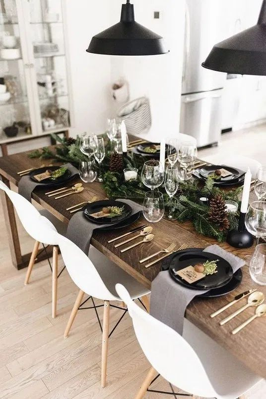 a Nordic rustic tablescape with an evergreen runner, pinecones, candles, black plates and grey napkins
