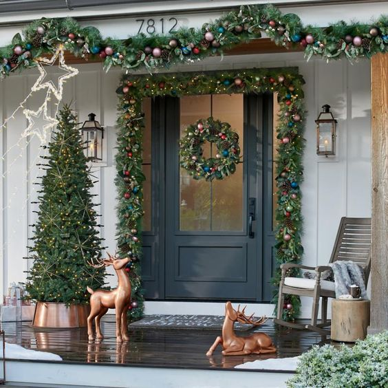 a bold Christmas porch with evergreen garlands with bold ornaments, copper deer, a Christmas tree with lights and star lights over the space