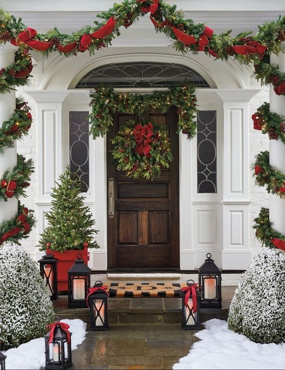 a bold and elegant Christmas porch with an evergreen lit up garland, a wreath with a red bow, a greenery and red ribbon garland, a mini tree, candle lanterns