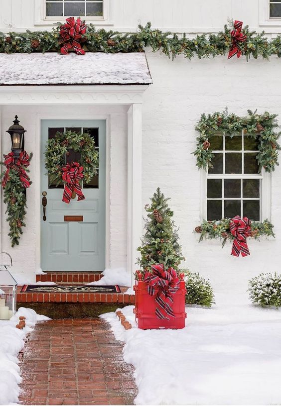 a bright Christmas porch with a mini tree in a red crate, evergreen wreaths and garlands, red striped bows is very cozy