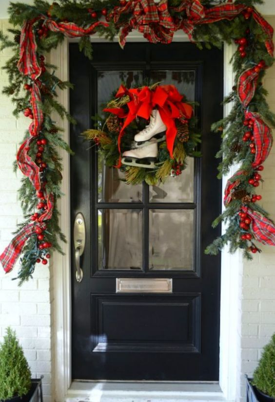a bright Christmas porch with an evergreen garland with berries, plaid ribbons, a wreath with a red bow and skates