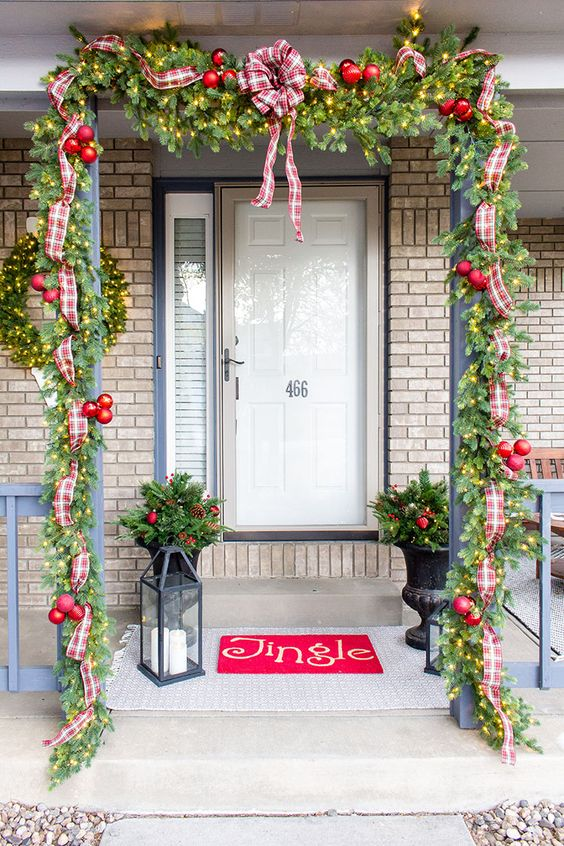 a bright Christmas porch with an evergreen garland with lights, red ornaments, plaid ribbons and bows, a red rug, candle lanterns and arrangements