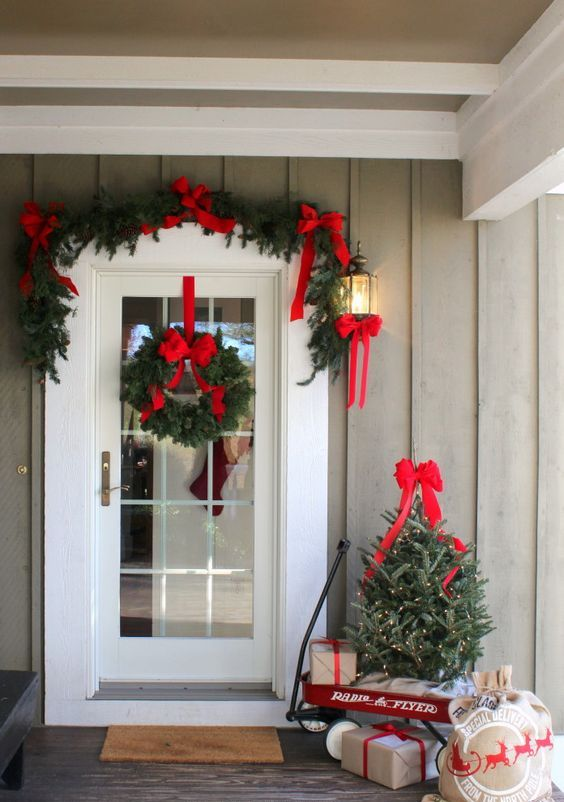 a bright and cool Christmas porch with an evergreen garland with red bows, a wreath, a mini tree with lights and gifts