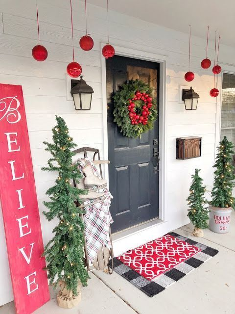 a bright and fun Christmas porch with red ornaments, mini lit up Christmas trees, a red sign and layered mats
