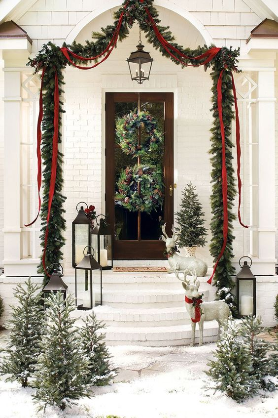 a charming Christmas porch with an evergreen and red ribbon garland, wild woodland wreaths, mini trees, candle lanterns and deer figurines