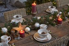 a chic Christmas tablescape with an evergreen and ornament runner, pillar candles, wooden stars and pinecones