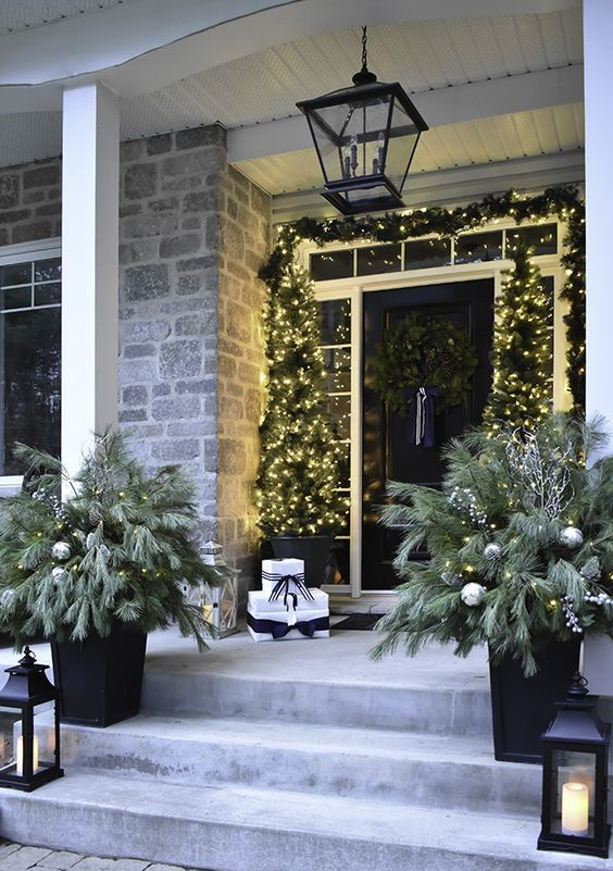 a chic black and white Christmas porch with mini Christmas trees and lights, a garland, snowy arrangement and candle lanterns
