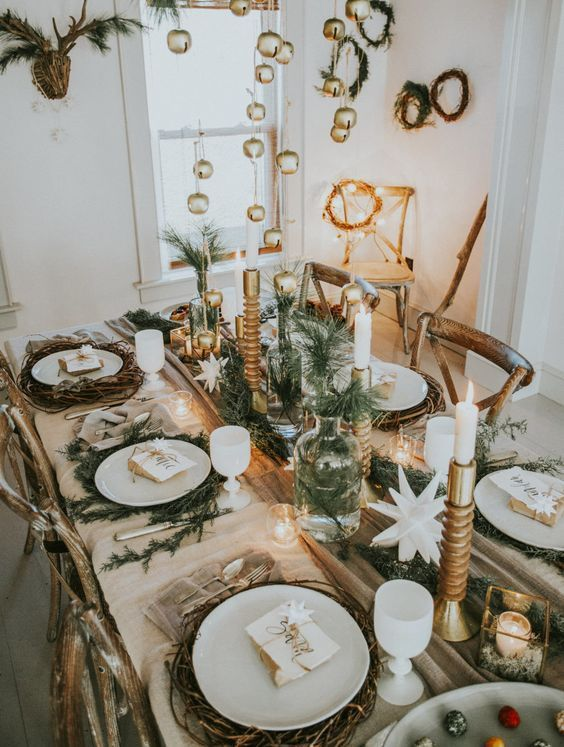 a chic rustic Christmas table with evergreens in bottles and vases, candles, woven placemats and bells hanging over the table