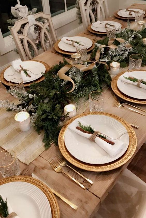 a chic rustic Christmas tablescape with gilded chargers, an evergreen runner with ribbons, pale branches, candles and cinnamon
