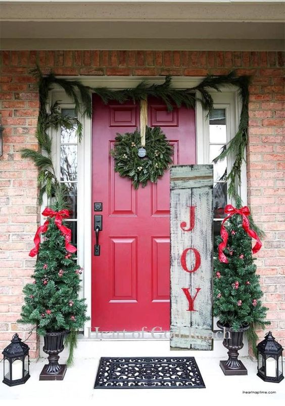 a colorful rustic Christmas porch with an evergreen wreath, mini trees with red bows and ornaments, candle lantens and a sign is very cool