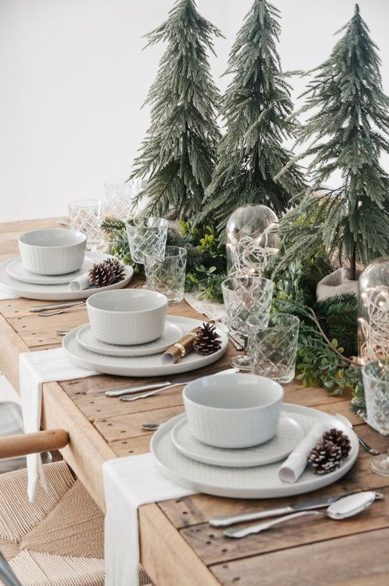 a cozy Christmas tablescape with mini trees, evergreens and greenery, white porcelain and pinecones plus white napkins