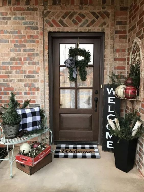 a cozy farmhouse Christmas porch with plaid linens, evergreens, bells and ornaments feels vintahe and rustic and invites in