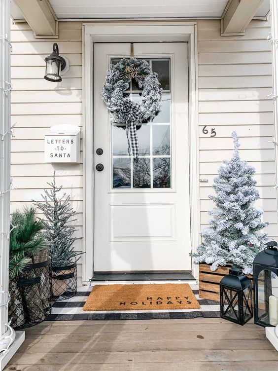 a farmhouse Christmas porch with snowy Christmas trees, candle lanterns, a snowy Christmas wreath is a veyr cozy space