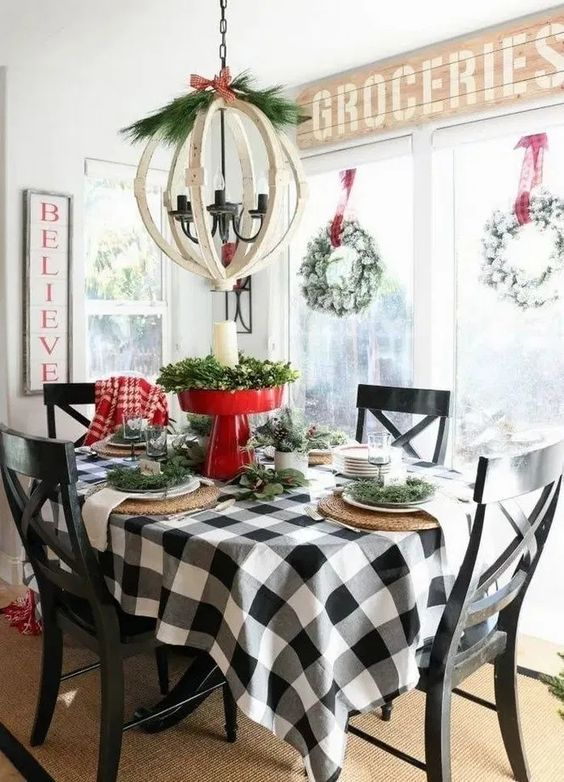 a farmhouse Christmas table with a plaid tablecloth, woven placemats, evergreens, a red stand with greenery and a pillar candle