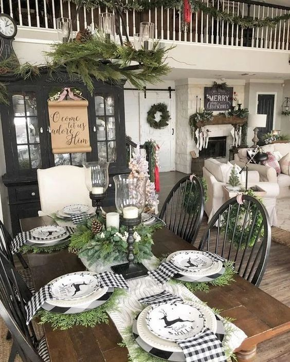 a farmhouse Christmas table with black and white plaid napkins, evergreens and deer printed plates plus candles in candleholders