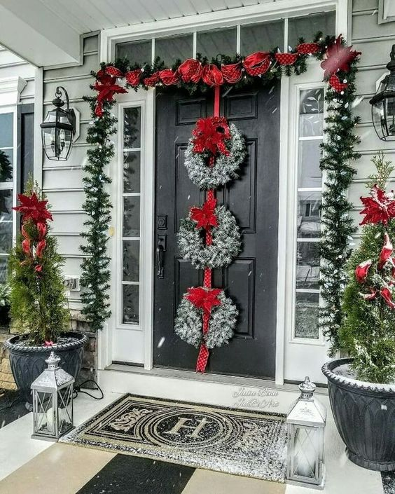 a festive Christmas porch with an evergreen garland with lights and red ribbons, snowy wreaths with red bows and mini Christmas trees