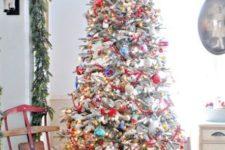 a flocked Christmas tree with colorful ornaments, lights and a red yarn star tree topper looks really vintage-like