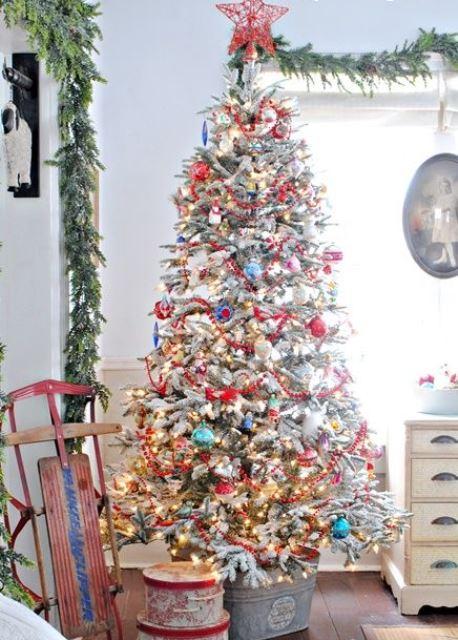 un arbre de Noël floqué avec des ornements colorés, des lumières et un topper d'arbre en fil rouge ressemble vraiment à un style vintage