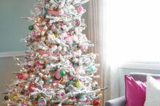 a flocked Christmas tree with lights, colorful ornaments, striped ribbons and frozen branches on the top