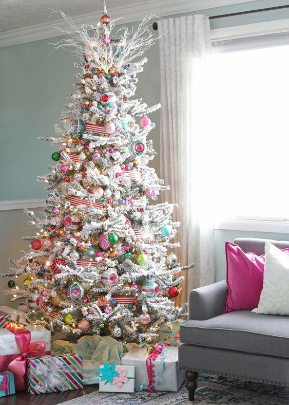 un arbre de Noël floqué avec des lumières, des ornements colorés, des rubans rayés et des branches gelées sur le dessus