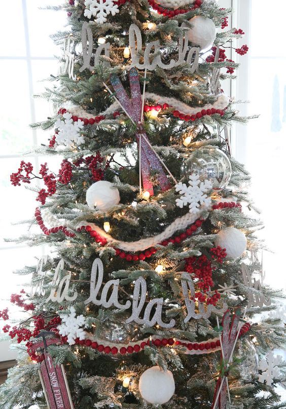a flocked Christmas tree with lights, cranberry garlands, letters, skis and sleighs is a chic vintage-inspired idea