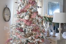 a flocked Christmas tree with oversized white and silver ornaments, red berries and striped ribbons plus lights