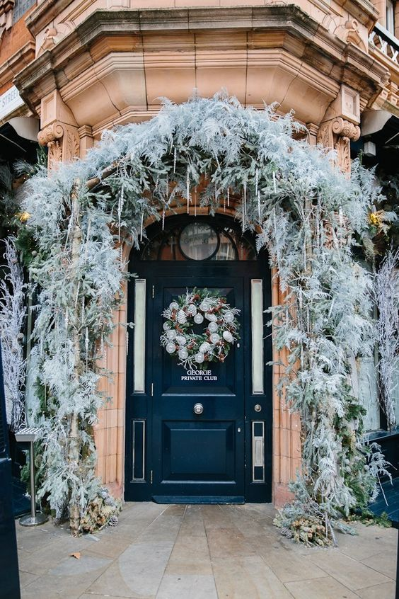 a frozen Christmas porch with pale leaves and greenery, icicles, lights, a wreath with lights and pinecones is lovely