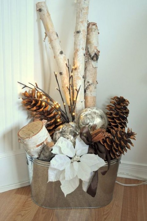 a galvanized bathtub with large pinecones, firewood, lights, ornaments and a fabric flower for Christmas decor