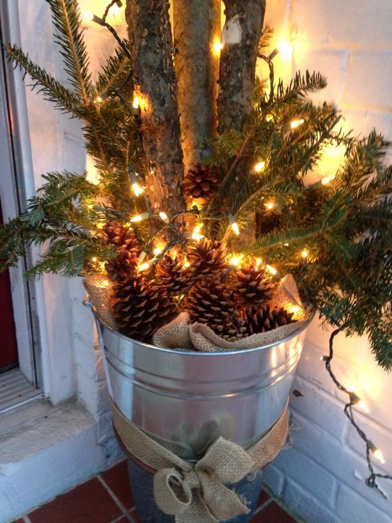 a galvanized bucket with burlap, pinecones, evergreens and branches is a cool rustic decoration for Christmas