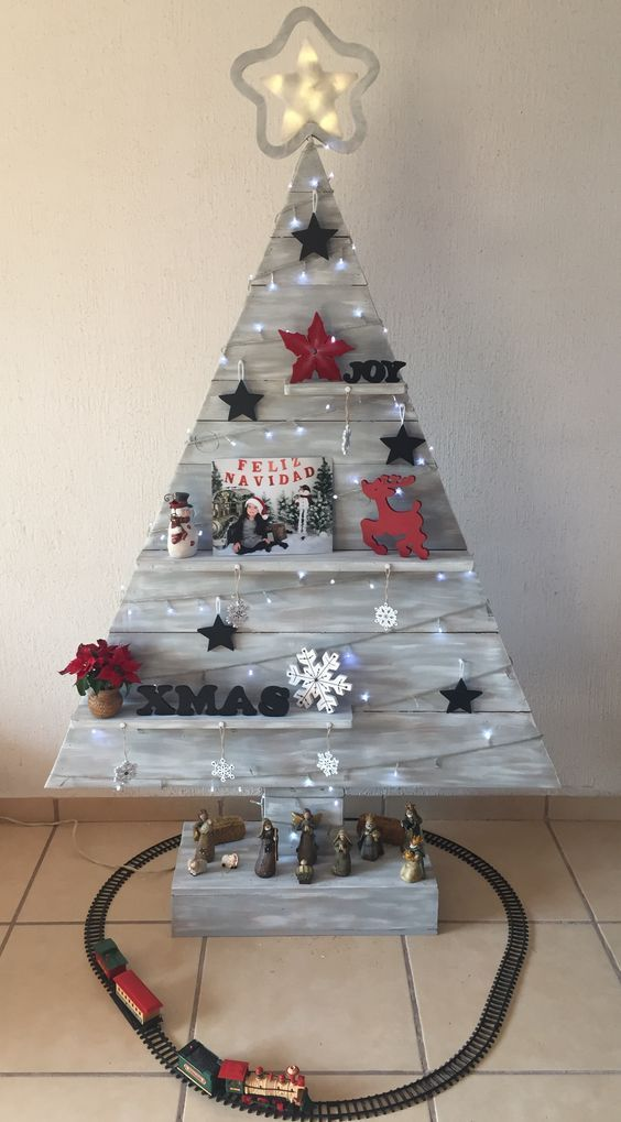 a grey rustic Christmas tree with shelves, stars, lights, letters, blooms and deer decorations