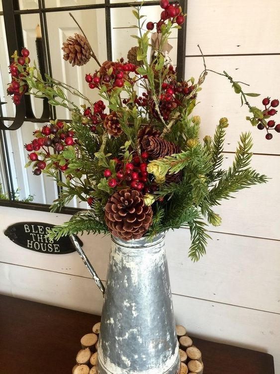 a metal jug with evergreens, pinecones, berries and greenery is a cool Christmas centerpiece