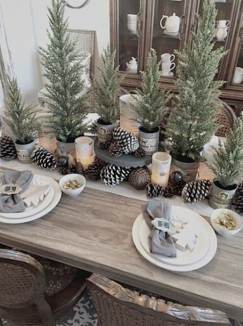 a modern rustic Christmas table with bells, pinecones, potted Christmas trees and wooden tree ornaments plus grey napkins