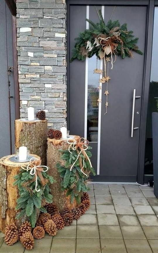 a modern woodland Christmas porch with tree stumps, evergreens, pinecones, candles and a matching posie on the door