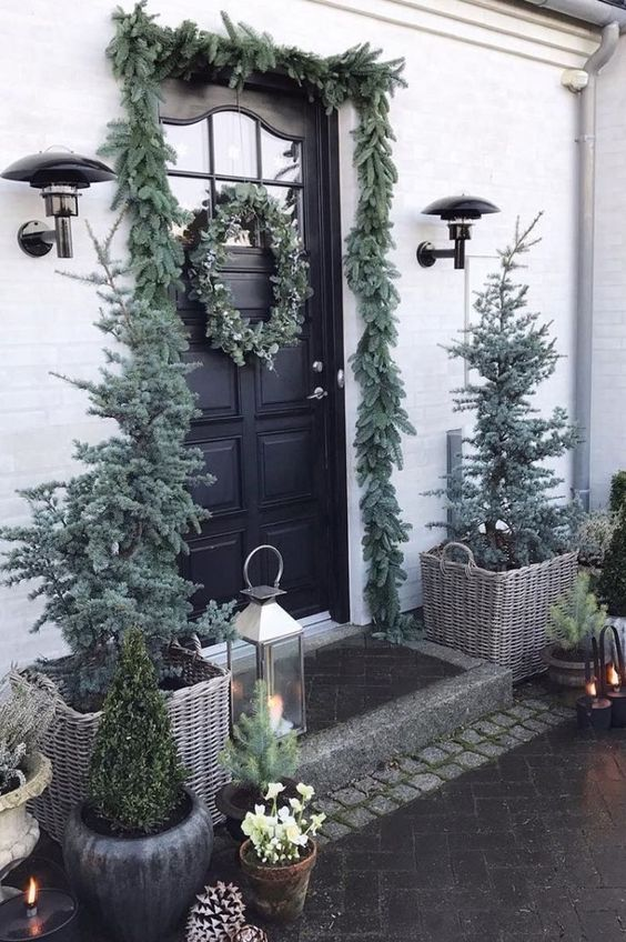 a natural Christmas porch with flocked Christmas trees in baskets, candle lanterns, mini trees and an evergreen garland over the door