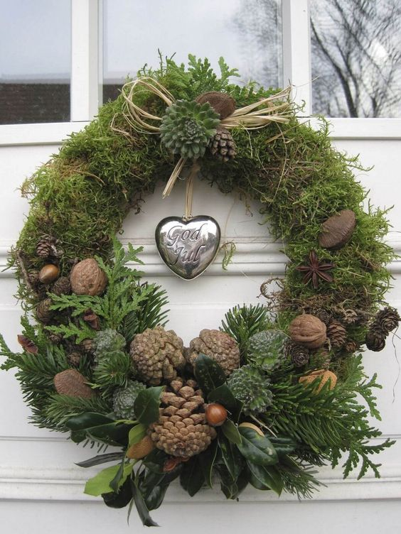 a natural Christmas wreath of moss, greenery, foliage, nuts, acorns, pinecones and a silver heart