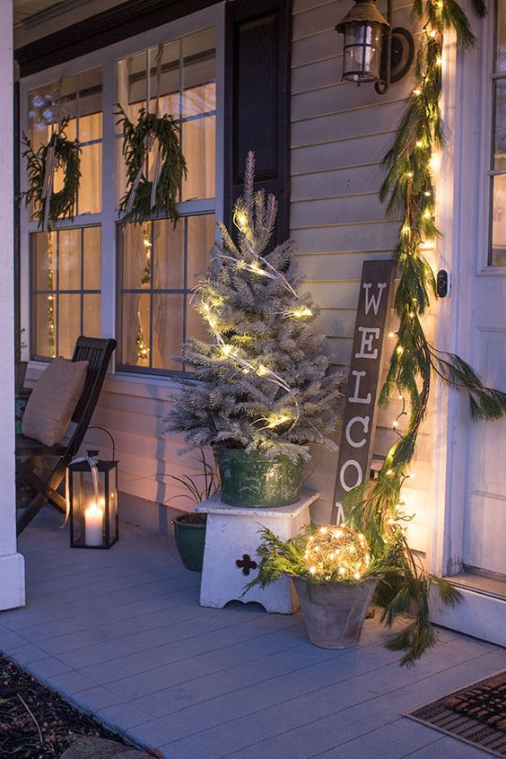 a neutral farmhouse porch with evergreen garlands, wreaths, lights, a snowy Christmas tree and candle lanterns is cozy and inviting