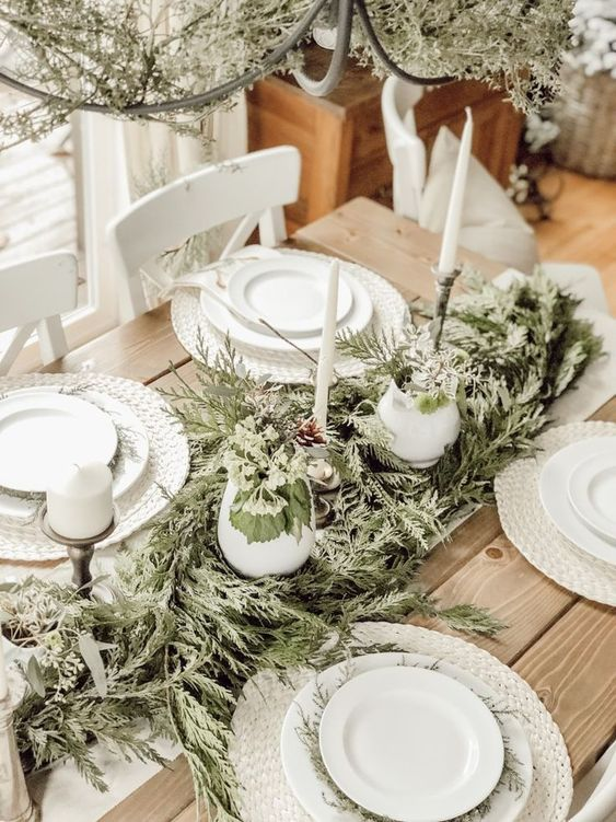 a neutral rustic Christmas table with white woven placemats, a greenery runner, tall candles and white porcelain
