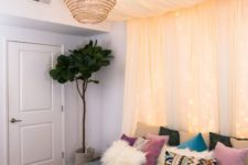 a pastel canopy with lights over the bed plus a wicker lampshade for a boho look