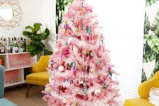 a pink Christmas tree with colorful ornaments and lights, with gold touches looks pretty and very chic