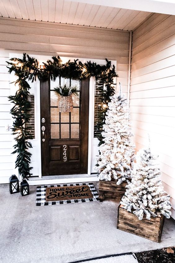 a pretty farmhouse Christmas porch with snowy Christmas trees in crates, an evergreen garland with lights over the door, candle lanterns