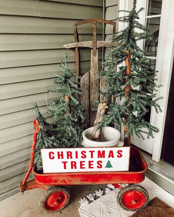 a red cart with a sign, three Christmas trees in buckets is a nice rustic porch decoration