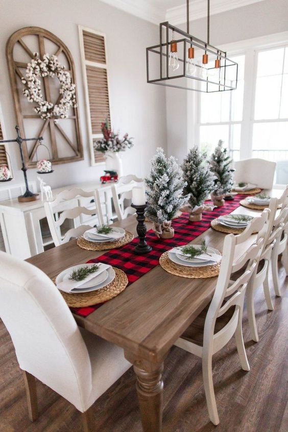 a red plaid runner, flocked Christmas trees in burlap, candles, woven placemats and evergreens on each place setting