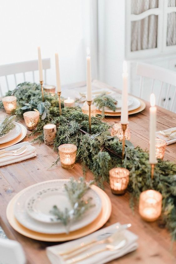 a refined rustic Christmas table with an evergreen runner, lots of candles, gilded chargers and evergreen touches