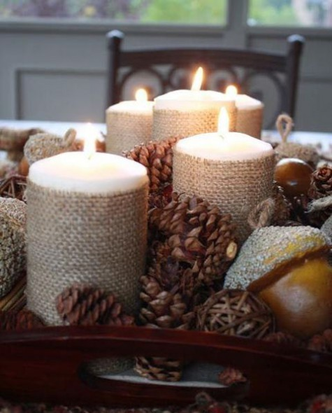 a rustic Christmas centerpiece of a tray, pinecones, vine balls, nuts, candles covered with burlap is a creative idea