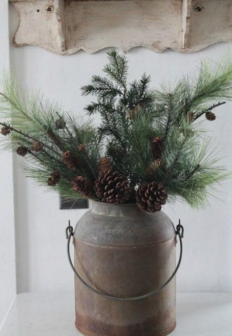 a rustic Christmas decoration of an old milk churn with evergreens with pinecones can be placed inside or outside