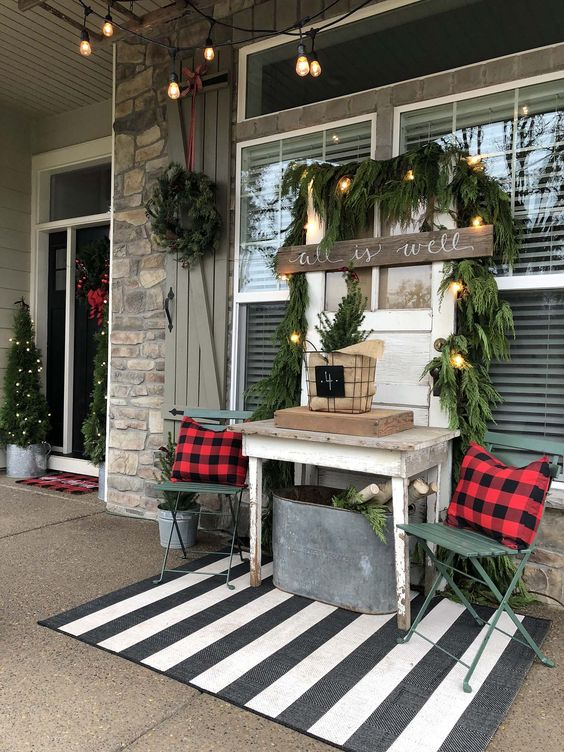 a rustic Christmas porch with evergreens, plaid pillows, a bucket with firewood, lights, a sign and trees framing the doorway