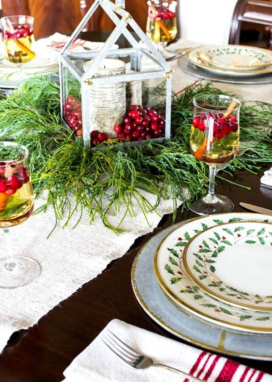 a rustic Christmas table setting with a fabric runner, evergreens, a lantern with berries and a stump candleholder plus printed porcelain